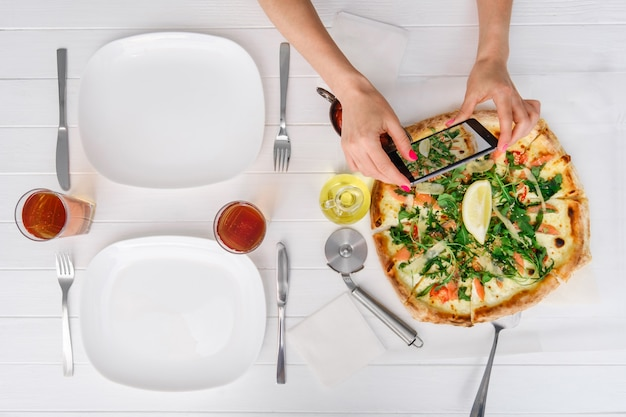 女性はピザの写真を撮る