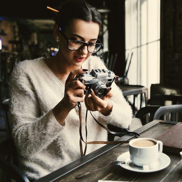 女は、カフェに座っているレトロなカメラで写真を撮る