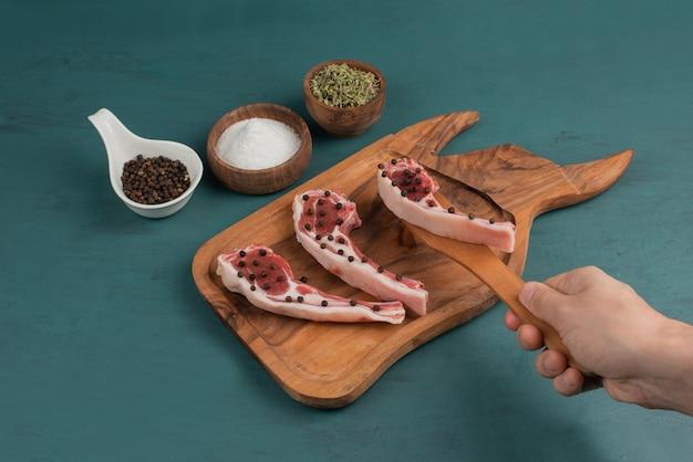 女性は木の板から未調理の肉片を取ります。