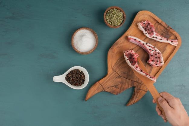 여자는 나무 보드에서 요리하지 않은 고기 조각을 걸립니다.