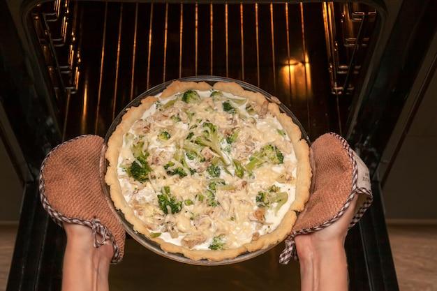 여자는 부엌에 있는 오븐에서 치즈를 뿌린 닭고기와 브로콜리를 곁들인 열린 쇼트브레드 파이를 가져간다