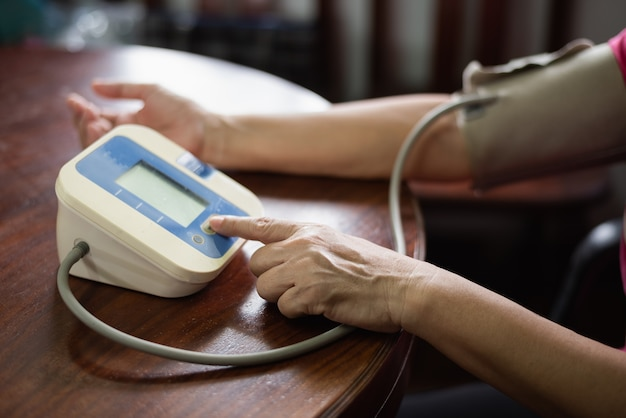 The woman takes care of her health by checking her blood pressure