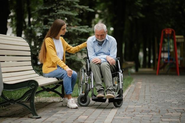 女性は車椅子で障害のある父親の世話をし、家族は公園を歩いています。麻痺した人と障害、ハンディキャップの克服。公共の場で障害のある男性と若い女性の保護者