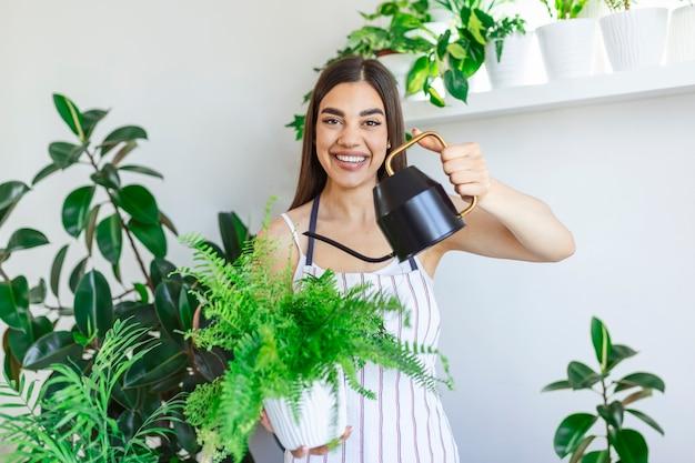 여자는 집에서 식물을 돌보고 검은 물통으로 물을 준다