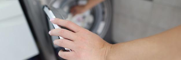 Женщина берет чистое белье из стиральной машины крупным планом
