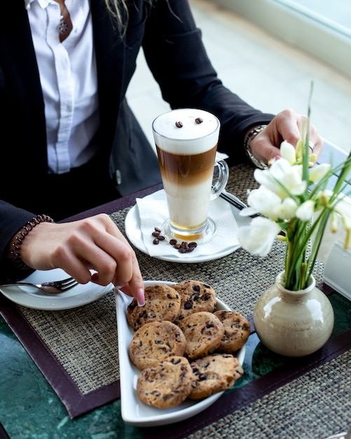 Woman takes cookie to eat with latte