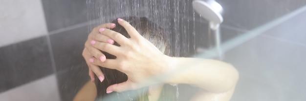 Женщина принимает горячий душ в ванной крупным планом