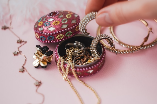 Женщина берет украшения из маленькой коробочки на розовом фоне