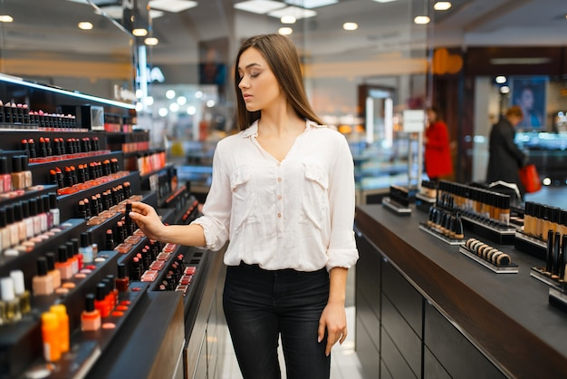 Woman takes lipstick from shelf in cosmetics store. buyer at the showcase in luxury beauty shop salon, female customer in fashion market