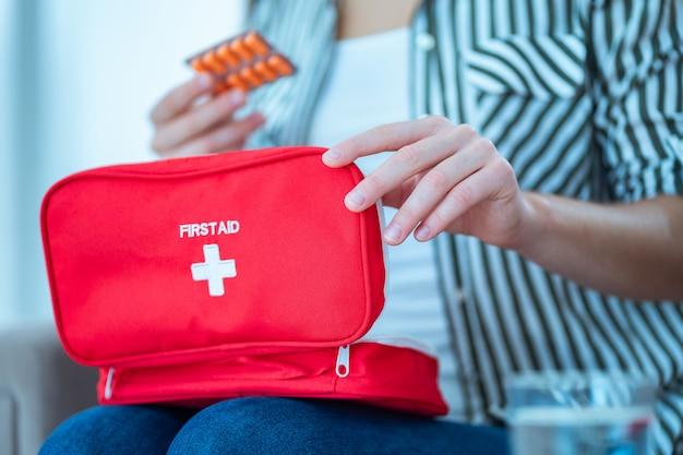 Женщина принимает лекарства от боли и болезней дома. медицинская аптечка