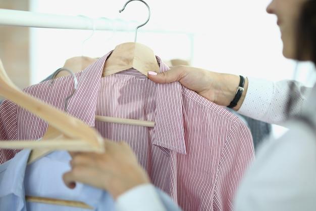 Женщина снимает и держит в руках вешалки с рубашками