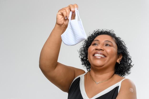 여성은 백신을 접종한 후 씹던 것을 벗고 행복하게 웃는다. 코로나19 예방접종