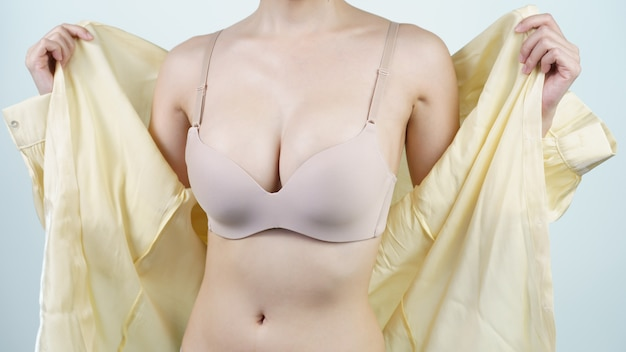 여자는 밝은 노란색 셔츠를 벗고 가벼운 누드 란제리를 입고 있습니다. 유방 임플란트 수술 개념.