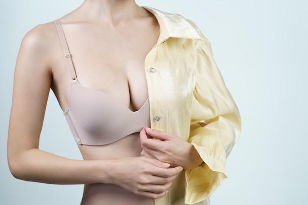 여자는 밝은 노란색 셔츠를 벗고 밝은 누드 란제리를 입고 있습니다. 유방 임플란트 수술 개념.