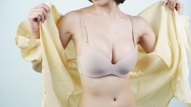 Woman takes off her light yellow shirt she is in light nude lingerie breast implant surgery concept