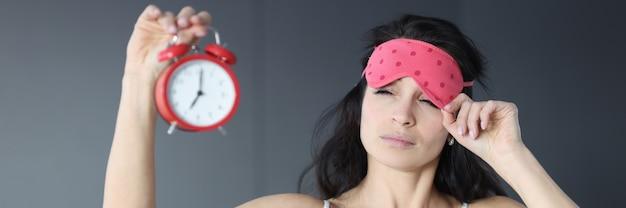 Женщина снимает маску сна и смотрит на будильник