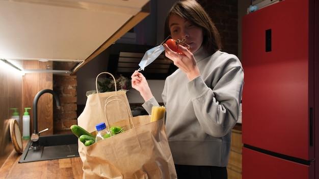 Женщина снимает маску, чтобы почувствовать запах свежих овощей на кухне