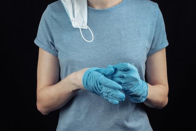 여자는 검은 벽에 의료 장갑을 벗고. covid-19 대유행 극복