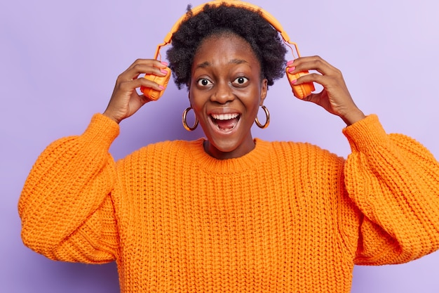 Woman takes off wireless headphones listens music with loud sound laughs happily wears orange knitted sweater enjoys favorite playlist isolated on purple