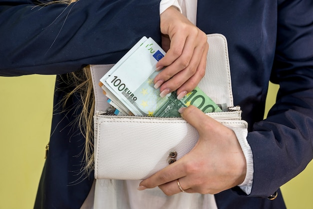Woman takes out euro banknotes from wallet on green
