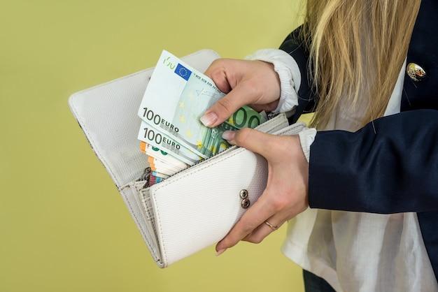 女性は緑の財布からユーロ紙幣を取り出します