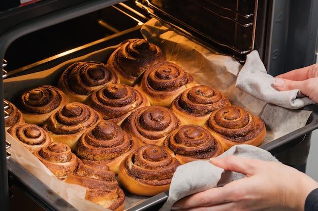 Женщина достает из духовки вкусные запеченные булочки с корицей с румяной корочкой