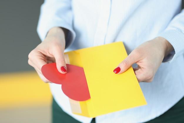 여자는 봉투 발렌타인 데이 인사말에서 붉은 마음의 형태로 발렌타인을 꺼내고