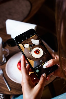 Woman takes photo of dessert on her smartphone