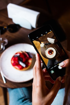 Woman takes photo of her dessert with smartphone