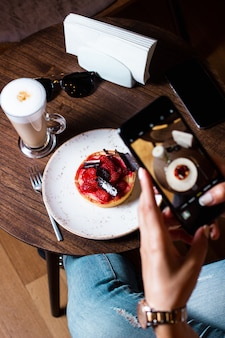La donna prende la foto del suo dessert alla fragola con il suo smartphone