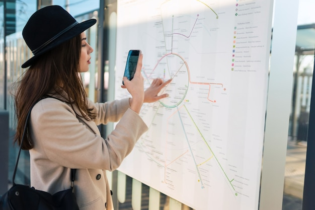 Woman takes photo of map public transport routes