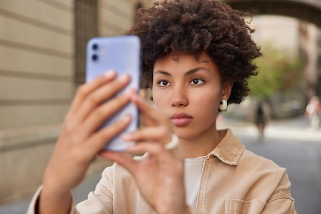 女性はソーシャルネットワークで共有するためにスマートフォンで自分の写真を撮りますカメラを注意深く見て街でレクリエーション時間を楽しんでいます