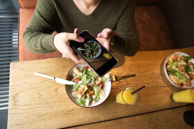 女性が食事の写真を撮ります。健康食品のコンセプト。上面図。ソーシャルネットワークの概念。