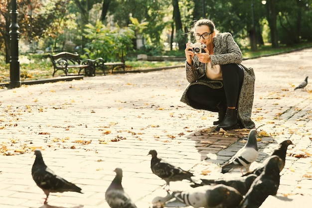Woman takes a photo of pigeons standing in the park
