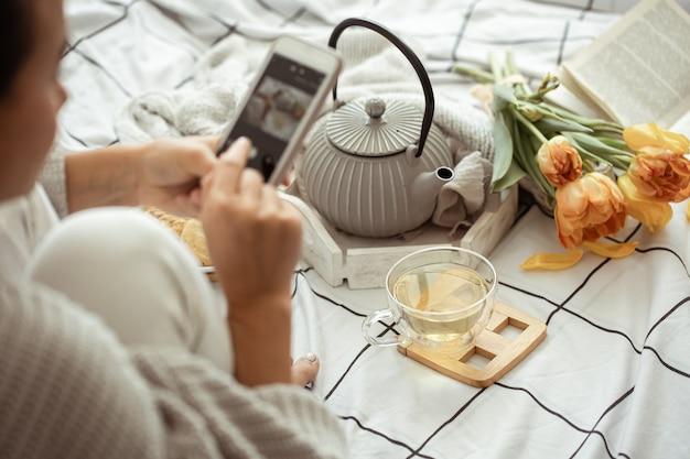 Женщина фотографирует на телефон весеннюю композицию с чаем, печеньем и тюльпанами в постели. концепция содержания социальных сетей.