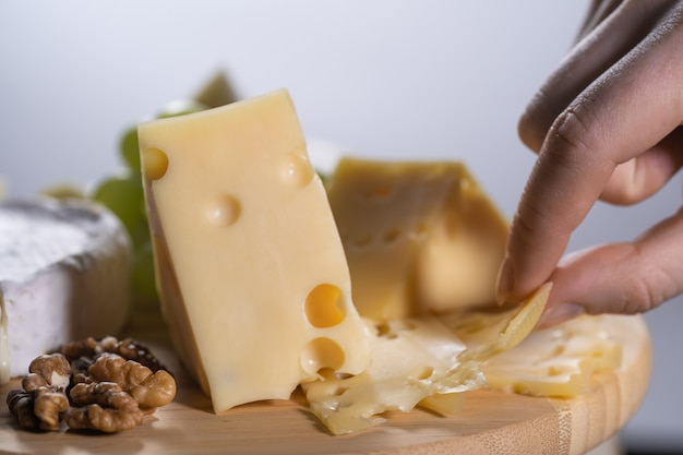 Woman takes a piece of maasdam cheese