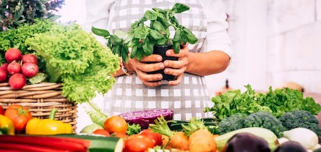 さまざまな野菜を使って台所で働いている女性は、手に植物を取り