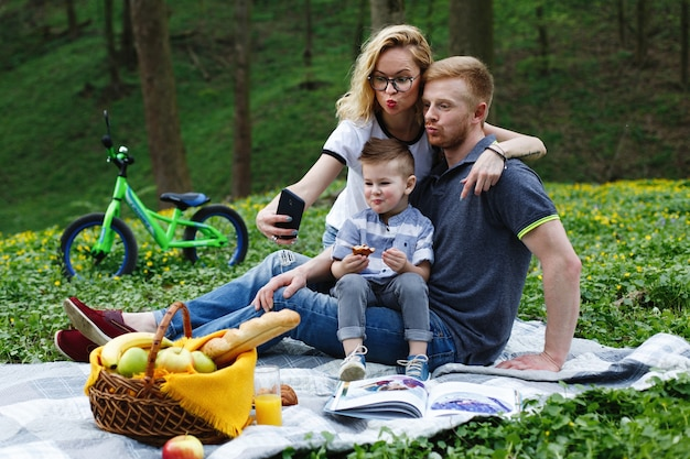 Woman takes a selfie with her parents and son sitting on a plaid in the park