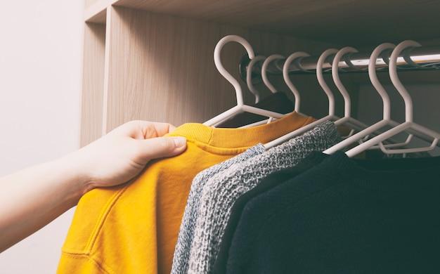 여자는 옷장에서 옷을 걸립니다.