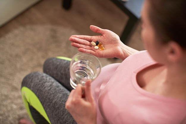 A woman takes vitamins during pregnancy. pregnant girl with a glass of water and a handful of drugs in her hand.