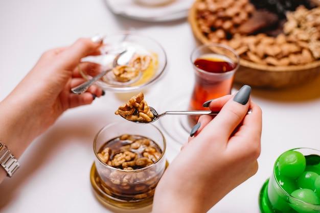 Женщина принимает ореховое варенье в блюдце чай сбоку