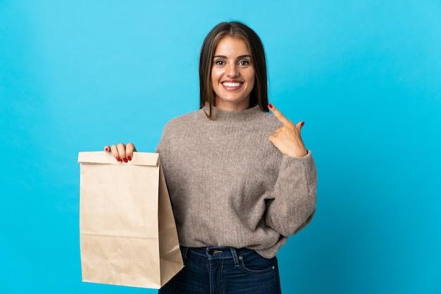 Женщина берет сумку еды на вынос, изолированную на синем, показывая большой палец вверх
