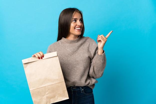 Женщина берет сумку с едой на вынос, изолированную на синем, намереваясь найти решение, поднимая палец вверх