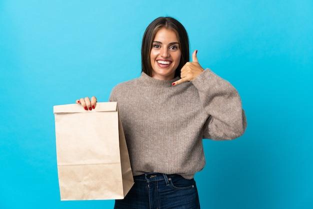 電話のジェスチャーを作る青で隔離の持ち帰り用食品の袋を取る女性。コールバックサイン