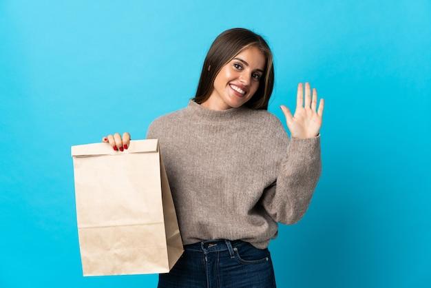 Женщина берет сумку еды на вынос, изолированную на синем приветствии рукой со счастливым выражением лица