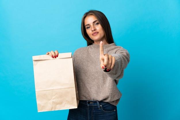 Женщина берет сумку еды на вынос, изолированную на синем, показывает и поднимает палец
