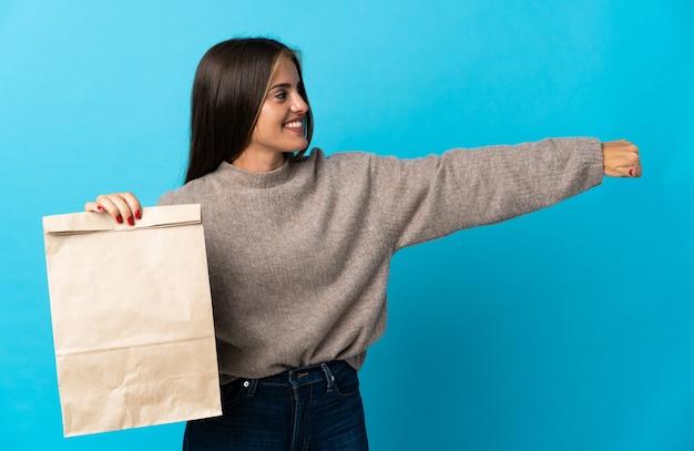 Женщина берет сумку еды на вынос, изолированную на синей стене, показывая большой палец вверх