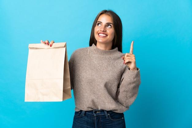 素晴らしいアイデアを指している青い壁に分離された持ち帰り用食品の袋を取っている女性