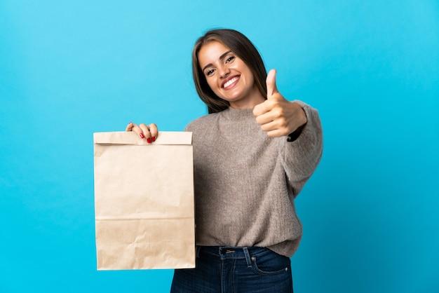 Женщина берет сумку с едой на вынос, изолированную на синем, с большими пальцами руки вверх, потому что произошло что-то хорошее