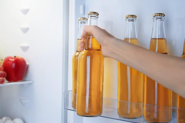Женщина берет бутылку лимонада из открытого холодильника